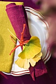 Place setting decoration with a serviette and yellow gingko leaves