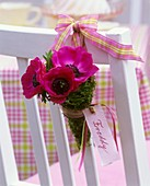 Posy of poppy anemones with place card (Freddy) hanging on chair