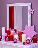 Sterne, Weihnachtskugeln und Kerzen vor einem Spiegel