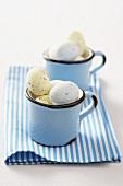 Gefärbte Wachteleier zu Ostern in zwei Emaille-Tassen