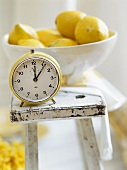 A bowl of lemons and an alarm clock on a stool