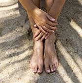 Frau sitzt im Sand (Nahaufnahme Füsse und Hände)