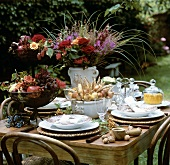Summery table decorated with flowers and fruit out of doors