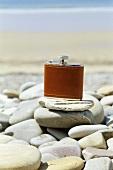 Hip flask on pebbles on beach