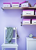 Labelled shoe boxes on shelves, chair, small cabinet