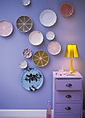 Decorative plates hanging on a lilac-coloured wall