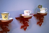 Old china cups and saucers on red plastic wall brackets