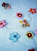 Pale blue fabric decorated with embroidery and fabric flowers