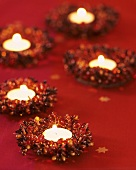 Five tealights in beaded wreaths on red tablecloth