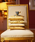 Stack of cushions and designer coffee cup and saucer on chair