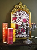 Colorful wrapping paper and antique candelabra in front of a gold frame containing a patterned paper