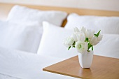 A bouquet of white tulip on a side table in a hotel room