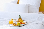 A breakfast tray on a bed in a hotel room
