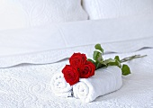 Red roses and two hand towels on a bed in a hotel room