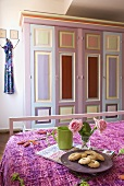 A tea break in a bedroom with a painted country house-style cupboard