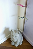 A stone animal figure and a paper butterfly in a corner of a room