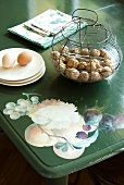 Nuts in a wire basket and eggs on a saucer on a painted table