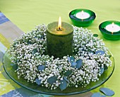 Wreath of gypsophila and eucalyptus around green candle