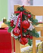 Fir branch with baubles and stars tied to chair back