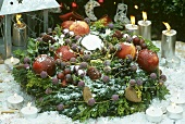 Wreath of fruit, nuts & conifer branches around a silver ball