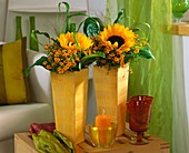 Sunflowers, tagetes and grasses in tall vases