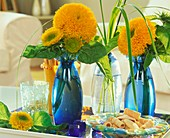 Double sunflowers in blue vases on tray