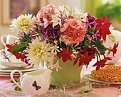 Vase of summer flowers on table laid for coffee