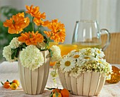 Table arrangements of Spanish poppies, viburnum & marguerites