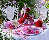 Laid table decorated with peonies and lilac