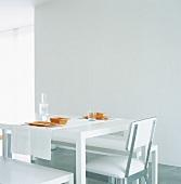 Ein weißer Esstisch mit orangem Geschirr gedeckt im sterilem Raum