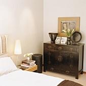 Alte Holzkommode mit Familienfotos und Lilienstrauß im Schlafzimmer