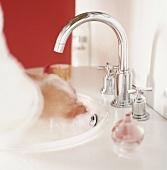 Person wäscht sich die Hände unter einem Edelstahlwasserhahn