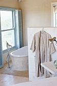 Badezimmer in beige mit Badewanne unter Fenster mit blauen Sonnenschutz von Innen