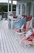 Gartenmöbel mit bunten Polster- und Sitzkissen auf einer Veranda