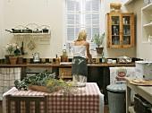 Frau beim Abwaschen in einer amerikanischen Landhaus-Küche mit Spülbecken unter dem Fenster