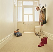 A toy and a clothes stand in an entrance hall