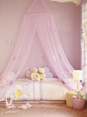 A child's room in pink with canopy over the bed
