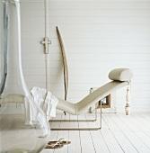 Ein Liegestuhl und Damenschuhe im weiß gestrichenen Holzhaus