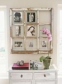 Altes Sprossenfenster onhe Fensterinsatz als Bilderrahmen üner Holzkommode mit Orchidee