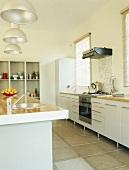 Eine Küche mit Kochinsel und Metallhängelampen darüber