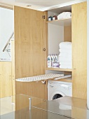 Washing machine, bath towels & ironing board in a cupboard