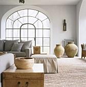 Ein helles Wohnzimmer mit grauer Couchgarnitur vor großes Rundbogenfenster und Backsteinboden