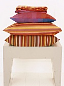 A pile of colourful cushions on a stool