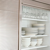 Plates and glasses in a kitchen cupboard
