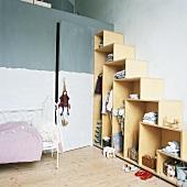 Kinderzimmer mit offenem Kleiderschrank in Stufenoptik, daneben ein weisses Metallbett und eine versteckte Zimmertür