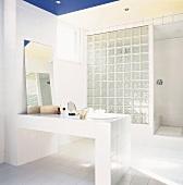 Bad mit gemauertem Waschtisch, angelehntem Badezimmerspiegel und einer Trennwand aus Glasbausteinen