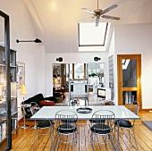 Esszimmer mit Deckenventilator über Metalltisch und -stühlen; zwei Schränke mit Spiegelfront umrahmen den Durchgang zur Küche