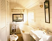 Small bathroom with white wooden walls, fitted cupboard with louver doors, large bathtub and maritime picture on wall