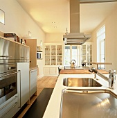 Well-equipped, modern kitchen with glass-fronted cabinets in background and appliances with stainless steel fronts
