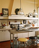 Kitchen with stainless steel counter and chrome bar stools; modern cooker with extractor in old fireplace